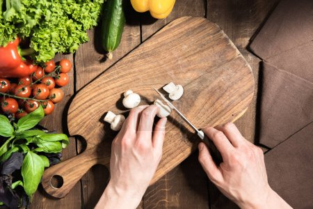 Hands cutting mushrooms on chopping board