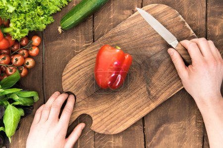 Photo for Top view of human hands cutting pepper on chopping board with group of veggies around - Royalty Free Image
