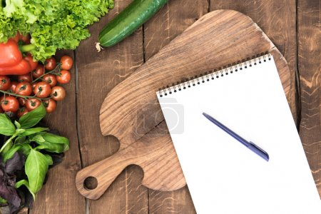 Photo for Top view of organic vegetables, chopping board and blank notepad with pen on wooden background - Royalty Free Image