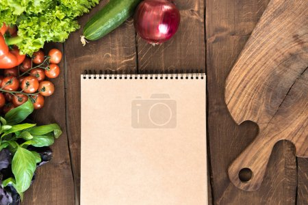 Photo for Overhead view of raw vegetables, chopping board and blank notepad on wooden table. Food composition background - Royalty Free Image