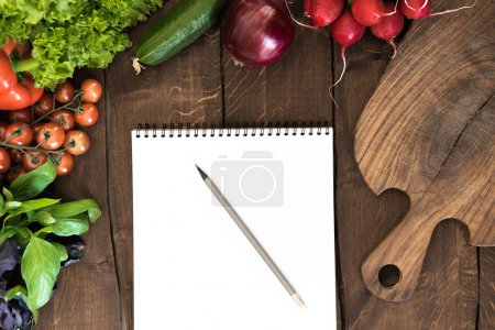 Photo for Top view of various vegetables with cutting board and blank notepad on wooden background - Royalty Free Image