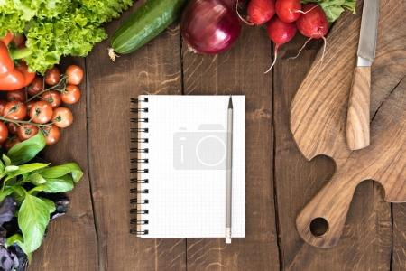 Photo for Top view of organic vegetables, chopping board and blank notepad with pencil on wooden background - Royalty Free Image
