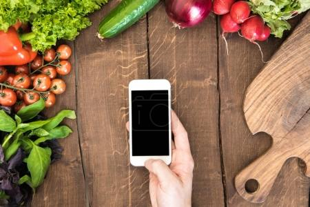 Photo for Top view of kitchen table full of various vegetables and human hand holding smartphone with blank screen. - Royalty Free Image
