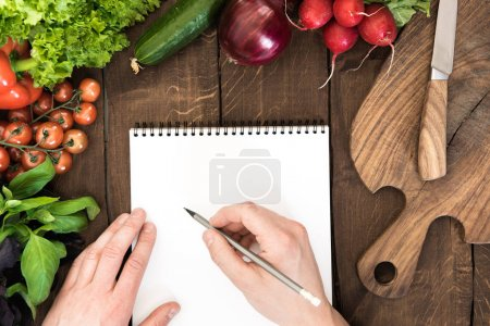 Photo for Food composition of raw vegetables, chopping board and human hand able to write something in notepad on wooden background - Royalty Free Image
