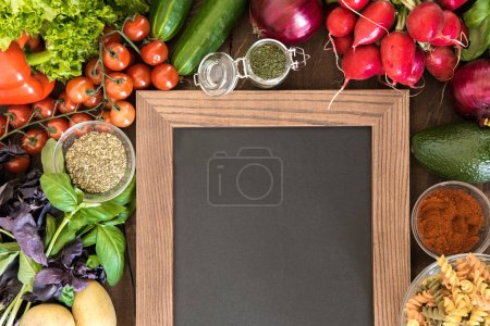 Photo for Blank chalkboard with set of ingredients and spices for cooking Italian pasta from above view. Food preparation background - Royalty Free Image