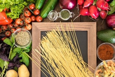Photo for Above view of food background with natural vegetables, spices and two types of Italian pasta on chalkboard - Royalty Free Image