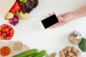 Smartphone over table with vegetables
