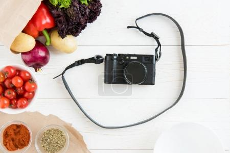 photo camera with vegetables and spices
