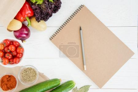 Notebook and vegetables on table