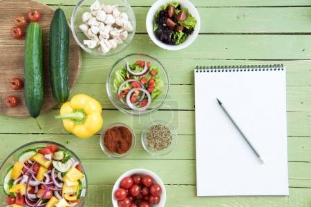 Photo for Top view of fresh raw vegetables and salads in bowls and blank notebook with pencil on wooden table - Royalty Free Image