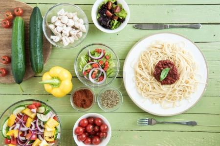 Photo for Top view of delicious spaghetti on plate and fresh raw vegetables on wooden table - Royalty Free Image