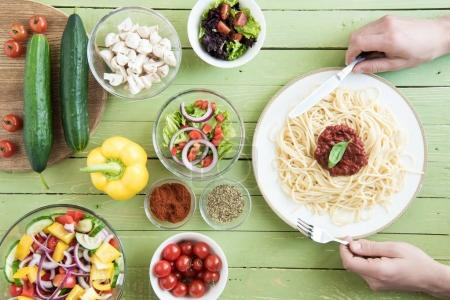 Photo for Close-up partial view of person holding fork and knife while eating spaghetti with sauce and basil and fresh raw vegetables on wooden table - Royalty Free Image