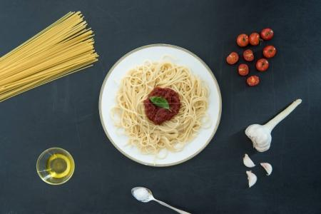 Photo for Top view of spaghetti with sauce, basil and ingredients on black - Royalty Free Image