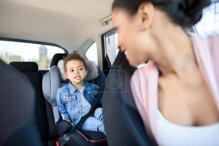 Photo pour Petite fille afro-américaine avec mère assise dans la voiture - image libre de droit