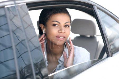 Photo pour Belle jeune femme dans les écouteurs assis dans la voiture et regardant la caméra - image libre de droit