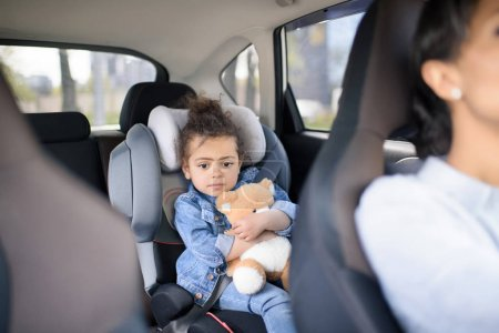 Girl with teddy bear in car