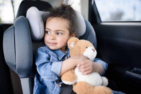 girl with teddy bear in car
