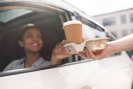 Photo for Portrait of woman sitting in car and buying coffee to go - Royalty Free Image