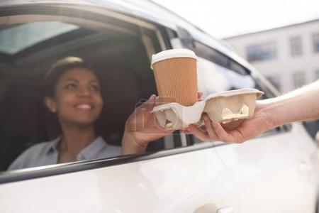 Photo pour Portrait de femme assise dans la voiture et l'achat de café pour aller - image libre de droit