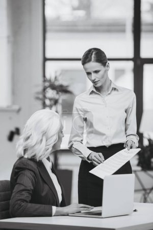 Photo for Businesswoman and her boss working with documents in office, black and white - Royalty Free Image