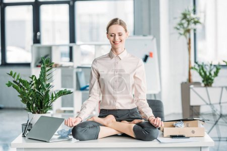 Photo for Happy businesswoman meditating in lotus position on messy table in office - Royalty Free Image