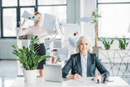 Photo for Smiling businesswoman sitting at workplace in office, stressed colleague with documents behind - Royalty Free Image