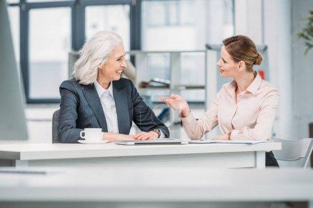 Foto de Dos empresarias discutir proyecto empresarial en la reunión en la oficina - Imagen libre de derechos