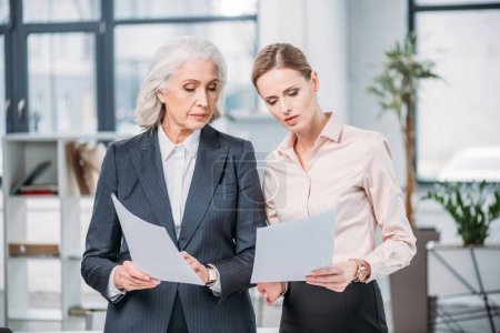 Photo for Two serious businesswomen standing and holding documents in office - Royalty Free Image