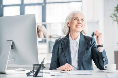 Photo for Cheerful senior businesswoman in formal wear sitting at workplace and triumphing - Royalty Free Image