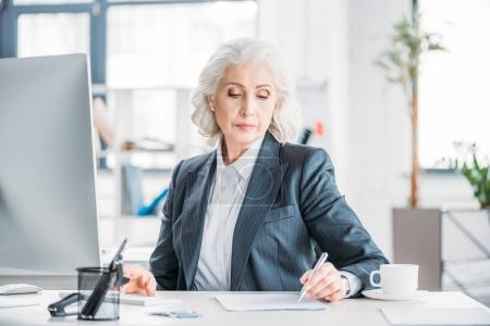 Photo for Confident senior businesswoman sitting at workplace and writing with pen - Royalty Free Image