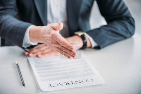 businesswoman with contract on tabletop