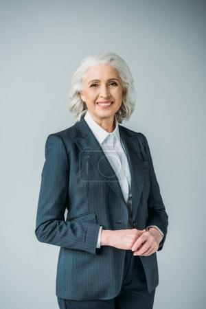 Photo for Portrait of smiling senior businesswoman in suit isolated on grey - Royalty Free Image