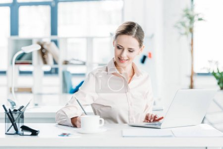 Photo for Young smiling caucasian businesswoman working on laptop at office - Royalty Free Image
