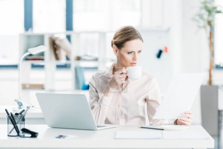 businesswoman working with documents and drinking coffee