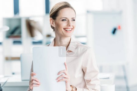 smiling businesswoman holding documents at office