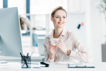 Photo for Young smiling businesswoman drinking coffee while sitting at office - Royalty Free Image