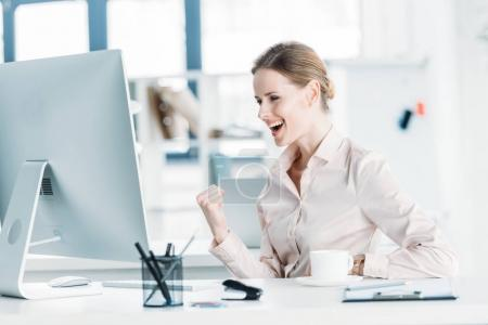 Photo for Young happy businesswoman sitting near modern computer at office - Royalty Free Image