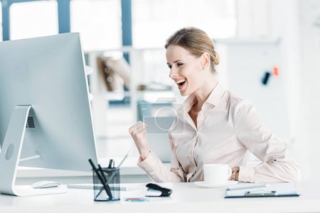 happy businesswoman sitting at office