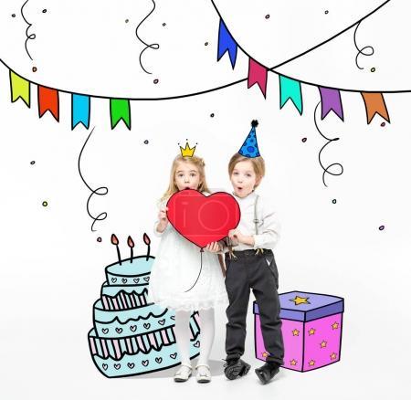 Foto de Poco niño y niña con corazón de papel rojo grande durante la fiesta de cumpleaños - Imagen libre de derechos