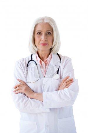 Photo pour Confiant médecin senior, regardant la caméra avec les bras croisés isolés sur blanc - image libre de droit