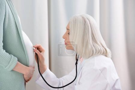 Doctor listening belly of pregnant woman