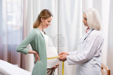 doctor measuring belly of pregnant woman