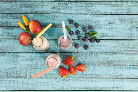 Photo for Top view of milkshakes in glass bottles with berries and fruits on wooden tabletop - Royalty Free Image