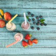 milkshakes in glass bottles with berries and fruits