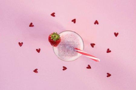 strawberry milkshake in glass with drinking straw