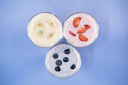 banana and berry milkshakes in glasses