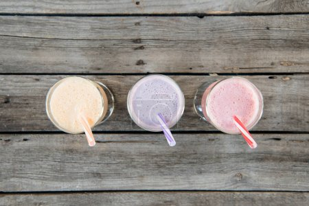 Photo for Top view of fruit milkshakes in glasses with drinking straws on wooden tabletop - Royalty Free Image