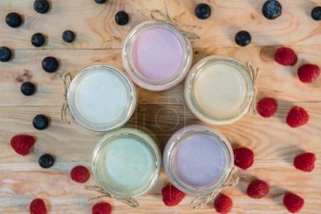 jars with berry milkshakes and berries