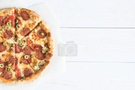 Photo for Top view of homemade delicious italian pizza on baking paper on wooden tabletop - Royalty Free Image
