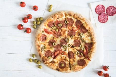 Photo for Top view of homemade italian pizza with sausages, cherry tomatoes and olives on wooden surface - Royalty Free Image